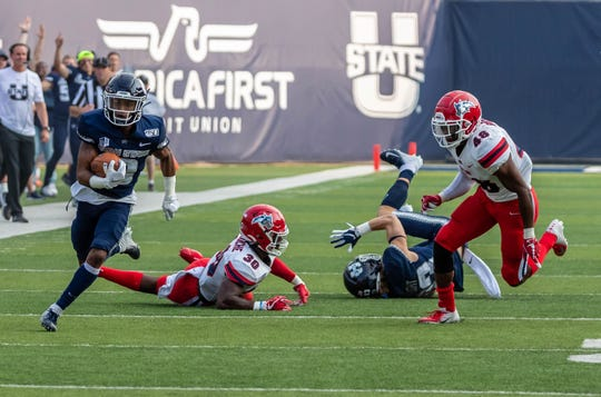 Dunbar graduate Deven Thompkins runs back a 45-yard punt return for a touchdown in Utah State's 62-7 victory over Stony Brook on Sep. 7.
