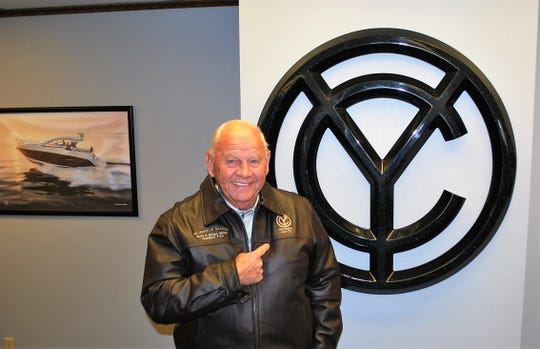 "Roger Stewart stands next to the Cruiser Yachts logo, near a framed photo of one of the company's boats, during his retirement party on July 30. He was given a leather jacket embroidered with the logo and the words ""60 years of service ... Over 6 million mles accident free"" to mark his success a driver."