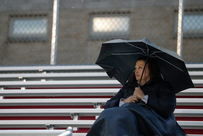 A fan sits in the rain during a soccer game between Green Bay East and Hortonville High School Thursday, September 12, 2019, at City Stadium in Green Bay, Wis.