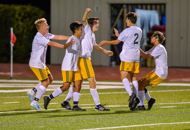 CMR's Blake Sowers, center, celebrates with teammates after scoring the winning goal in this season's first crosstown soccer match against Great Falls High.