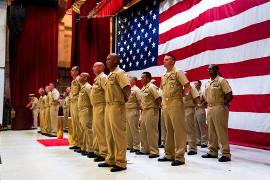 U.S. Navy petty officers and one U.S. Air Force technical sergeant from multiple Guam based commands stand at parade rest during a chief petty officer pinning ceremony held Sept. 13 onboard Naval Base Guam.