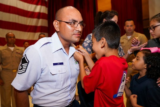 Air Force Tech. Sgt. Gabriel Lira, assigned to the 30th Naval Construction Regiment, is pinned to the rank of chief petty officer by his son during a CPO pinning ceremony onboard Naval Base Guam. The ceremony consisted of a total of 29 Sailors and one Airman promoted to the paygrade of CPO with a total of 46 CPOs island wide.
