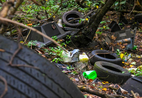Old tires and other discarded items are shown in the jungle near the Chalan Pago Bridge in this Sept. 13 file photo. Rainwater that collects in tires and other items can act as a breeding ground for mosquitoes.