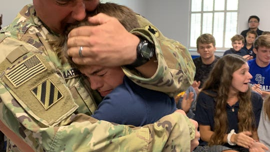 Brad Marrero Sr. hugs his son Brad Marrero Jr. on Friday, Sept. 13, 2019, at Sacred Heart School in Hattiesburg after his return from a yearlong deployment in Kuwait.