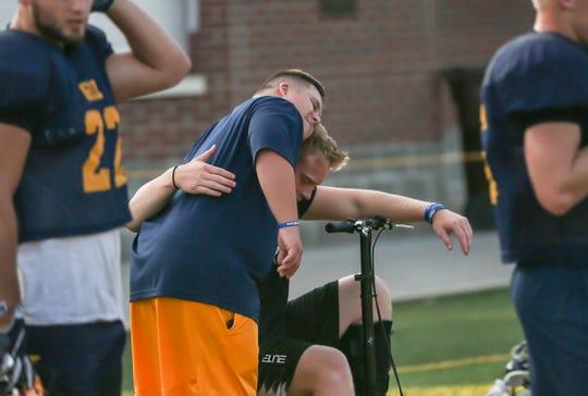 Emry Himes hugs injured linebacker Kray Leininger during practice.