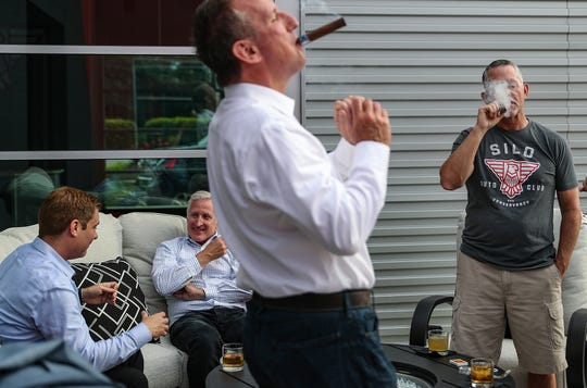 Right, owner Mike Simmons and other members enjoy cocktails and cigars during a themed member night at Silo Auto Club and Conservancy in Indianapolis, Thursday, Aug. 22, 2019.