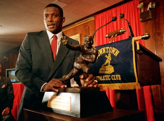 FILE - In this Dec. 5, 1987 file photo, Notre Dame's wide receiver and kick return specialist Tim Brown poses with the Heisman Trophy at New York's Downtown Athletic Club. Brown was a tremendous player, but he won the Heisman by being a great decoy. He had 990 yards from scrimmage and scored all of seven touchdowns.