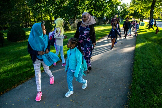 A group of families who live in the Mormon Trek Village area, which is about 1.5 miles from Weber Elementary, walk to school, Friday, Sept. 13, 2019, along Rohret Road in Iowa City, Iowa.