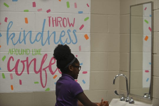 Mariah Warren, a sixth grader at East Elementary in Humboldt, smiles in the mirror and washes her hands in  front of wall art that was painted in the girls' bathroom by the nonprofit organization, Heart of Whimsy.