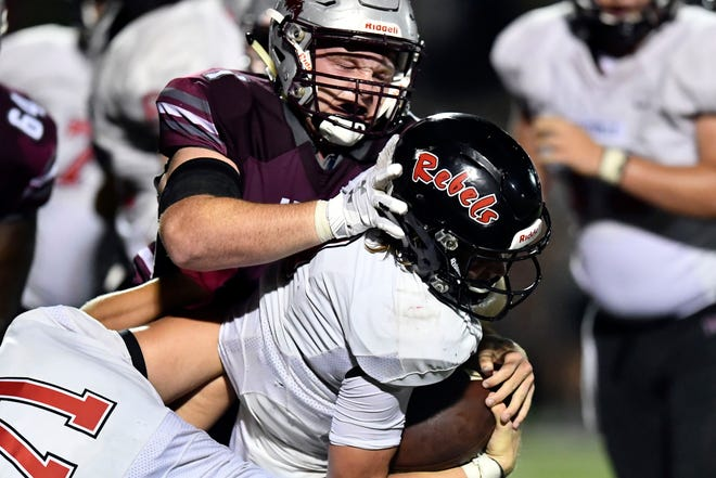Maryville's Cade Chambers (9) is taken down by Alcoa's Grey Carroll (1) on Thursday, September 12, 2019.