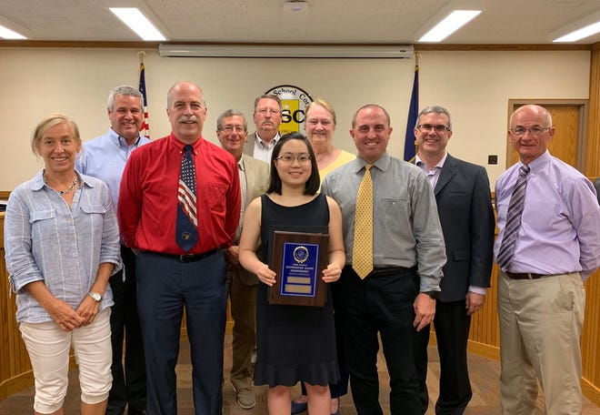 Harrison junior Song Kim, center, with her award commemorating her as the only student in the state to receive a perfect cumulative score during the Indiana Math League.