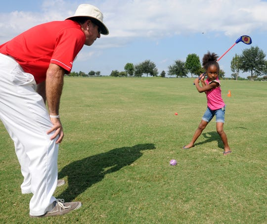 Former UL and pro pitcher Jose Alvarez, left, watches as Ariyanna Green, 6, swings during the Fellowship of Christian Athletes TourLife Youth Golf Clinic at The Wetlands Saturday, Sept. 24, 2011, in Lafayette.