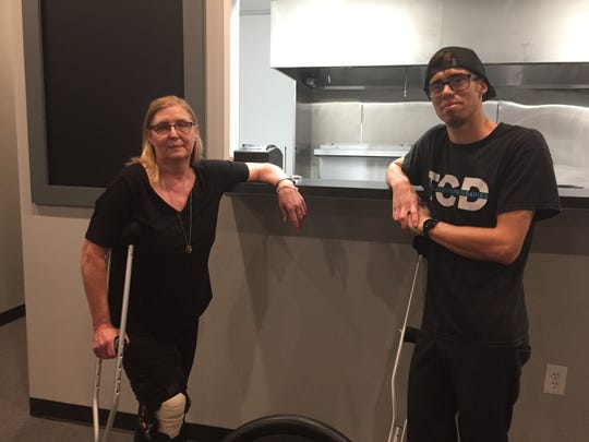 Recovering from knee surgery isn't going to stop restaurateur Sandra Blake, pictured with her grandson Andrew Sharpe, from reopening her Mexican eatery as soon as possible. She holds herself up on crutches at Mexicali and More, shown Friday, Sept. 13, 2019.