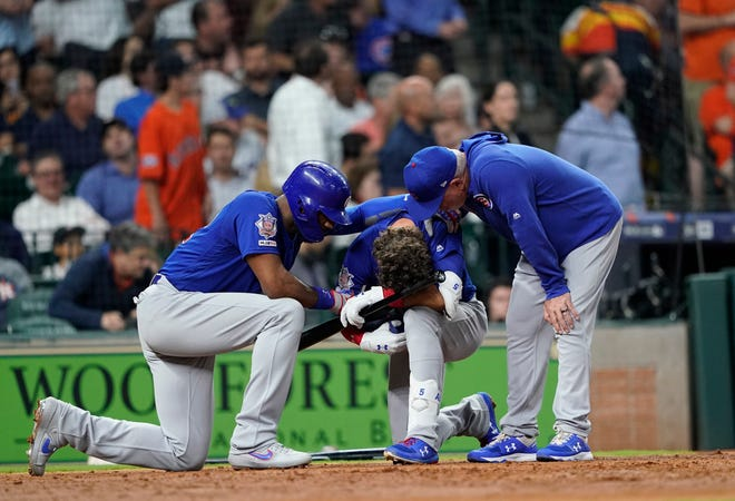 The Chicago Cubs' Albert Almora Jr. takes a knee as Jason Heyward, left, and manager Joe Maddon console him after his foul ball  struck a young child in a game May 29 in Houston.