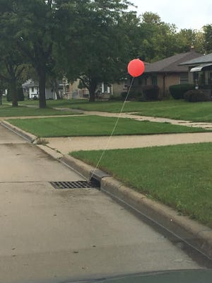 """Red balloons, the calling card of Stephen King's Pennywise in """"IT,"""" were found tied to sewer grates throughout Cudahy on Friday the 13th. This balloon was spotted on Nicholson Avenue."""
