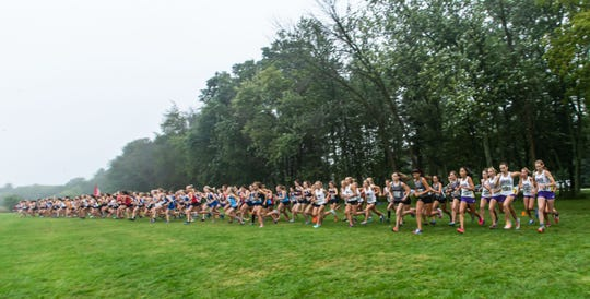 Competitors burst off the starting line for the varsity girls 5000 meter race at the Arrowhead Cross Country Invitational in Hartland on Thursday, Sept. 12, 2019.