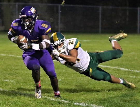 Martin Luther linebacker Fred Guytoon attempts to bring down Racine Lutheran running back Jaylen Houston during a game on Sept. 12, 2019.
