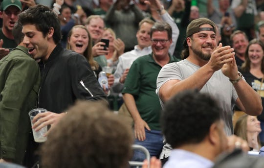 Milwaukee Brewers outfielder Christian Yelich, left, basks in the cheers of fans after chugging a beer while Green Bay Packers offensive tackle David Bakhtiari, right, applauds during the second half of their NBA Eastern Conference finals game Thursday, May 23, 2019 at Fiserv Forum in Milwaukee, Wis. The. Toronto Raptors beat the Milwaukee Bucks 105-99.