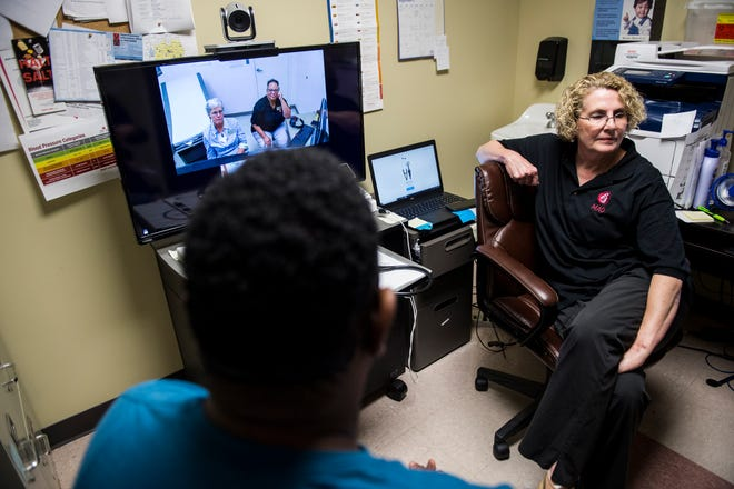 Rita Jennings, RN, left, sits down with Larry, an HIV patient at the Medical Advocacy and Outreach office in Selma, Ala., on Wednesday, Sept. 4, 2019. MAO Medical Director Dr. Laurie Dill, MD, AAHIVS, and Assistant Medical Director Dr. Marguerite Barber-Owens, MD, AAHIVS are seen on the secure video call from Montgomery.