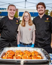 BJ's Brewhouse employees, from left, Cody Armbruster, Alexis McKissack and Paul Keating stand by the restaurant's Hickory Brisket and Bacon Burger at the 2019 Battle of the Burger.