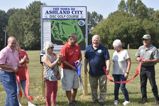 "Ashland City officials and Kentucky-based Disc Golf Course Senior Designer HB Clark gathered at the new disc golf course, around the John C. ""Preacher"" Poole walking track."