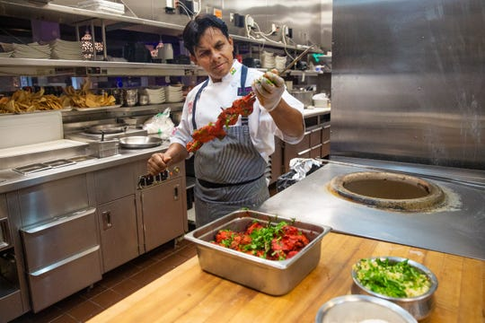 Chef Asif Syed skewers chicken breast at his restaurant 21 Spices on Friday, September 13, 2019 in East Naples.