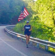 Claudia Kretschman runs with the American flag in Ringwood to honor victims of 9/11 on Sept. 11, 2019.