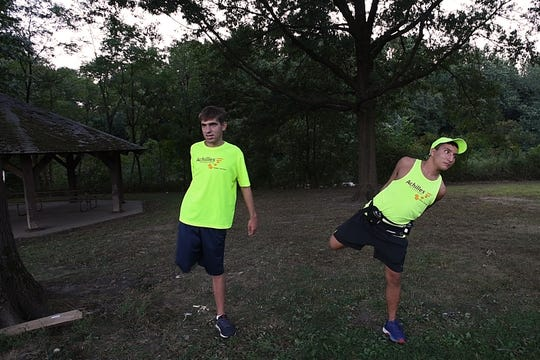 (left) Matty Monaco and Brandon Ehrlich stretch before a training run with the New Jersey chapter of Achilles in Saddle River Park on Wednesday, September 11, 2019. Achilles helps athletes with disabilities compete in races.