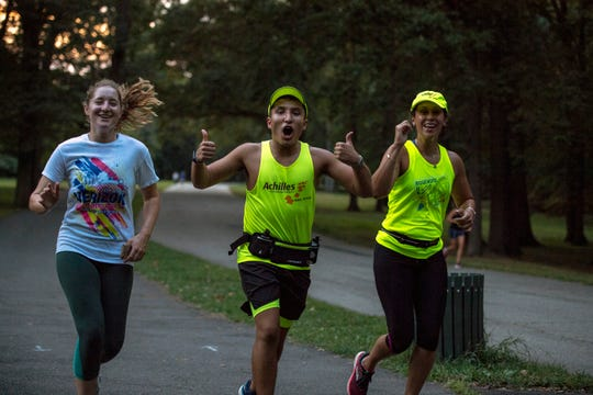 (center) Brandon Ehrlich runs with guides (left) Caroline Atkinson and Stephanie Munoz during a training run of the New Jersey chapter of Achilles in Saddle River Park on Wednesday, September 11, 2019. Achilles helps athletes with disabilities compete in races.