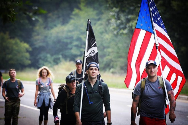 Capt. Matthew Carpenter, 14th Student Squadron, 14th Flying Training Wing graduation officer, carries the POW/MIA flag as he marches with Maj. Jonathan Leetch, 41st Flying Training Squadron T-6 instructor pilot, right, as they march 100 miles from Joint Base McGuire-Dix-Lakehurst, N.J. to the 9/11 Memorial in New York City.