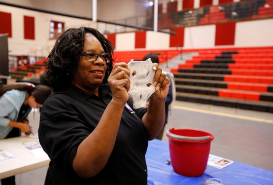 Priscilla Mobley, activity manager for the NASA Minority University Research and Education Project Aerospace Academy, shows how a sock should be cut during an activity to demonstrate liquid cooling ventilation garments at the NASA STEM Day on Sept. 12, 2019 at Navajo Technical University in Crownpoint.
