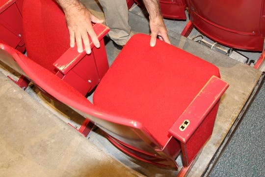 San Juan College senior physical plant director Chris Harrelson displays the seating in the Little Theatre that will be replaced when a renovation of the facility begins early next year.