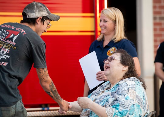 Karin Duff shakes hands with firefighter Isaac Lawrence during a ceremony at S.A.V.E.S in Conewago Township on Sept. 10, 2019. Lawrence was one of several first responders who assisted Duff when she went into cardiac arrest on July 27.