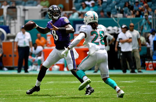 Baltimore Ravens quarterback Lamar Jackson (8) attempts a pass under pressure from Miami Dolphins cornerback Bobby McCain (28) during the first half at Hard Rock Stadium.