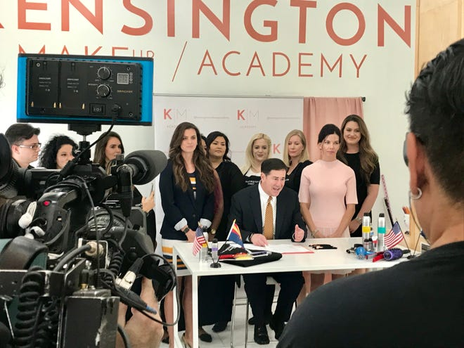 Gov. Doug Ducey, flanked by students at the Kensington Academy, ceremoniously signs a bill easing restrictions on people who style hair using blow dryers on Sept. 13, 2019. State Sen. Michelle Ugenti-Rita, (right) sponsored the bill.