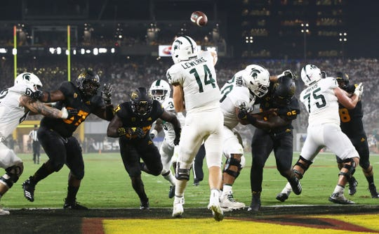 Michigan State quarterback Brian Lewerke throws a pass with pressure from Arizona State on Sep. 8, 2018, at Sun Devil Stadium.