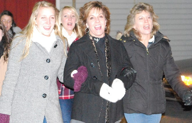 In this Dec. 2010 photo,  then Palmyra High School senior Devon McKain, Palmyra High School Key Club advisor Linda Bare and Palmyra High School English teacher Barb Mellinger lead the high school's Key Club down Railroad Street singing holiday songs. Bare, a former special education teacher and administrator, was a beloved figure in the Palmyra community and passed away in June after a bout with ovarian cancer. The Palmyra field hockey team is  paying tribute to Bare by hosting its Cougars for a Cure game vs. Red Land on Wednesday at 4 at In The Net.