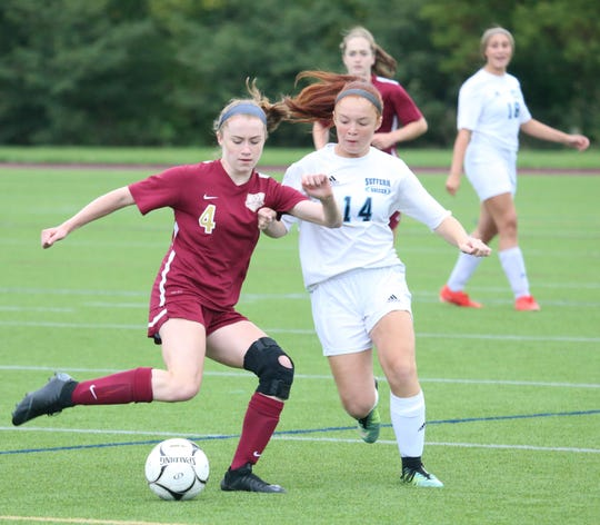 Arlington's Megan Stowell clears the ball away from Suffern's Alexis Farro during Thursday's game on September 12, 2019.