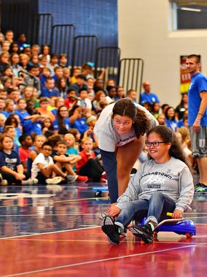 Dallastown's Kyiana Baker, right, is guided by Langley Brockway during a relay competition as Unified Sports teams up with Dallastown Area Intermediate School during a pep rally at the school in Springfield Township, Friday, Sept. 13, 2019. Dawn J. Sagert photo