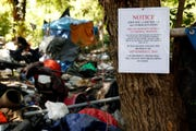 An eviction notice is pinned to a tree in front of a homeless camp on private land north of Wallace Marine Park in Salem in August 2019.