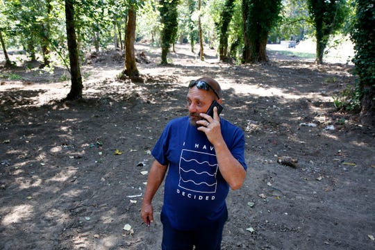 Former homeless camper Dean Ford talks on the phone while walking through private land north of Wallace Marine Park in Salem, Oregon, on Friday, Aug. 16, 2019. Ford lived in the woods around the park off and on for a decade, and in this area for several years.