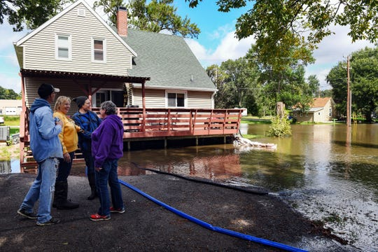 The Litkas and their extended family take a break from cleaning up floodwater outside a home on Friday, September 13, in Dell Rapids.