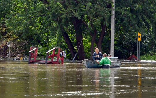 Matt Ellefson, Ceejay Douglas and Rick Williams pull a boat with personal belongings through flood water while the front porch stairs of Williams' home floats away behind them on Friday, September 13, in Dell Rapids.