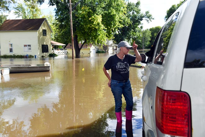 Tami Drew, one of the leaders of the flood relief efforts, speaks to a homeowner who had to evacuate on Friday, September 13, in Dell Rapids.