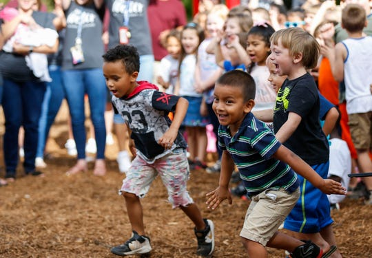 Weller Elementary School students run for the new playground after the ribbon was cut on Friday, Sept. 13, 2019.