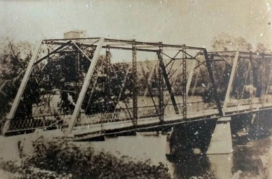 This is a historic photo of the Riverside Bridge when it was still located near the Ozark Mill at McCracken Road. It was moved to the north in 1924, near the site of the former Riverside Inn. This same bridge was disassembled in the fall of 2018 and will be put back together again near its original location at the mill. It will be part of a Johnny Morris development called Finley Farms.