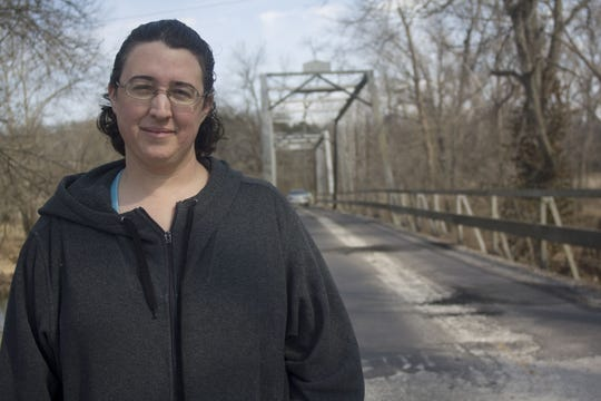 Kris Dyer stands at the approach to Riverside Bridge at  the Finley River in Ozark. She headed the Save the Riverside Bridge Initiative. She is pleased at how things have turned out. The one-lane bridge, built in 1909, has been dis-assembled and will be put back together again as part of a Johnny Morris development in Ozark called Finley Farms. The bridge will once again span the Finley River.