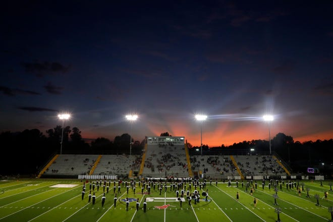 The sun sets behind Gene Cox Stadium as the Navarre High School band performs during halftime of a game between the Raiders and the Lincoln High School Trojans Thursday, Sept. 12, 2019.