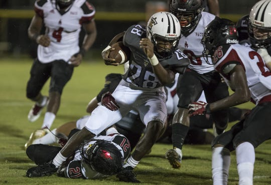 Eden James of Treasure Coast High School runs through the tackle of Terrence Hayes (bottom) of Monsignor Pace High School during their game at South County Regional Sports Stadium Thursday, Sept. 12, 2019, in Port St. Lucie. The Titans defeated the Spartans, 37-6.