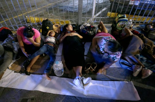 A group of Mexican migrants sleep at the base of the Paso del Norte Bridge where they are staging in hopes of making it to the United States.